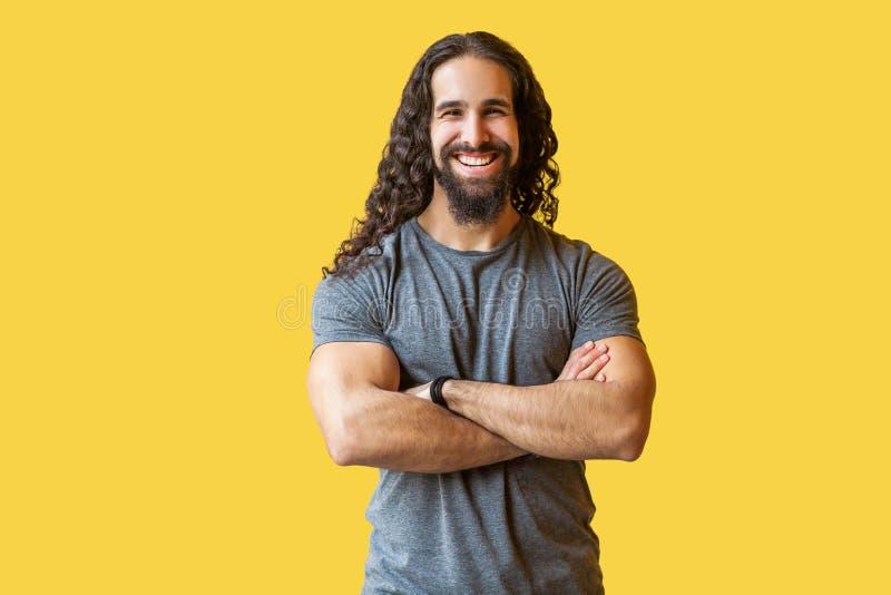 Retrato del hombre joven barbudo feliz hermoso con el pelo rizado largo en la situación gris de la camiseta con los brazos cruzad fotos de archivo libres de regalías