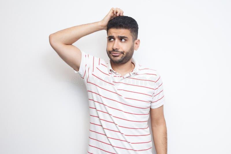 Retrato del hombre joven barbudo hermoso de la pregunta en la situación rayada de la camiseta que rasguña su cabeza, acepillando  foto de archivo
