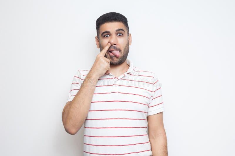 Retrato del hombre joven barbudo loco divertido en la situación rayada de la camiseta, lengua hacia fuera, perforando su nariz y  imágenes de archivo libres de regalías