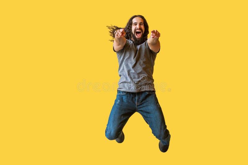 Retrato del hombre joven barbudo sorprendido con el pelo rizado largo en la camiseta gris que salta, señalando y mirando la cámar foto de archivo