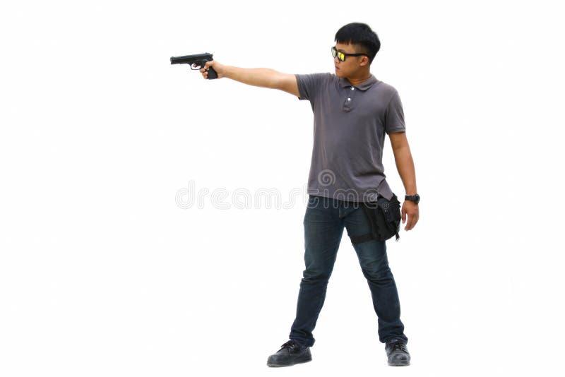 Retrato del hombre joven con el arma en el fondo blanco foto de archivo libre de regalías