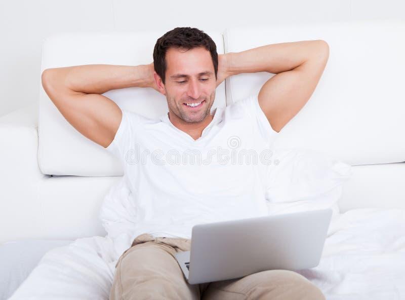 Retrato del hombre joven con la computadora portátil fotos de archivo
