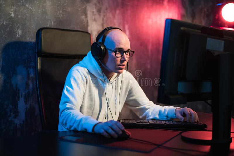 Retrato del hombre joven concentrado en vidrios y auriculares en el sitio oscuro que juega al juego de ordenador en línea o que c fotos de archivo libres de regalías
