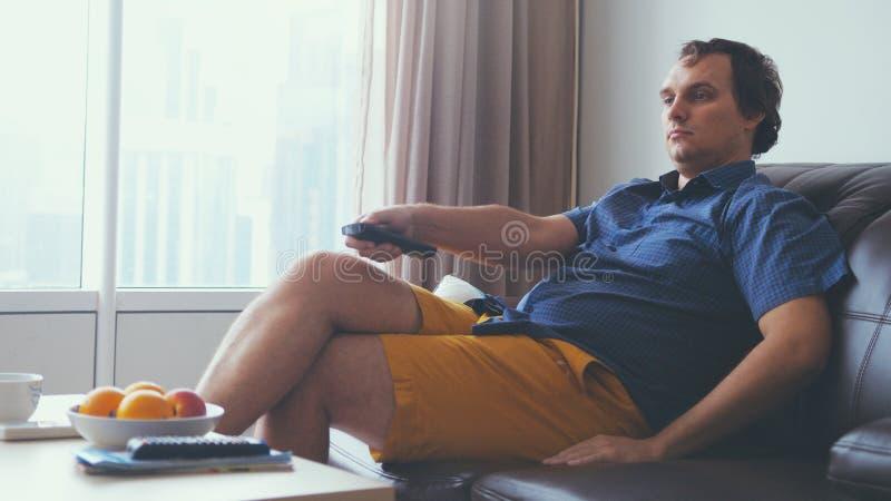 Retrato del hombre joven concentrado que se sienta en el sofá en sala de estar y programa interesante de observación de la TV imágenes de archivo libres de regalías