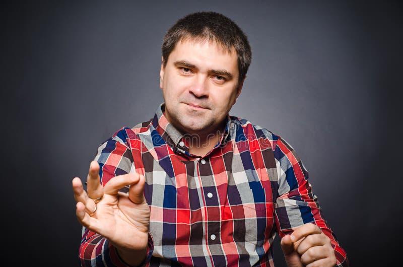 Retrato del hombre joven de gesticulating por las manos imagen de archivo