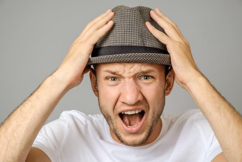 Retrato del hombre joven de griterío enojado imagen de archivo