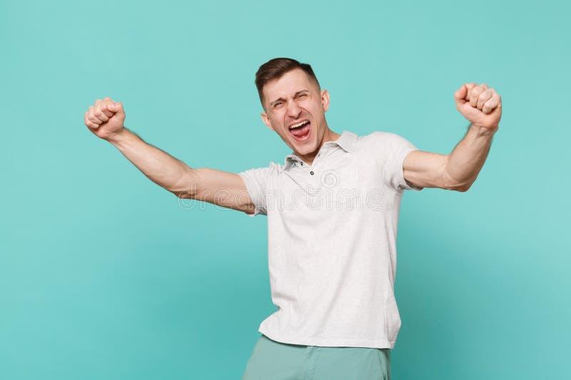 Retrato del hombre joven de griterío extático en puños de apretón de la ropa casual como el ganador aislado en la turquesa azul fotografía de archivo