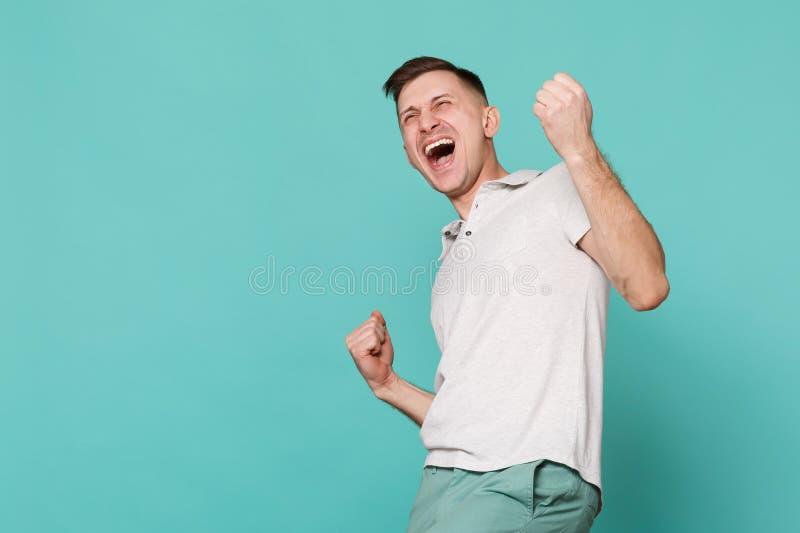 Retrato del hombre joven de griterío extático en puños de apretón de la ropa casual como el ganador aislado en la turquesa azul imágenes de archivo libres de regalías