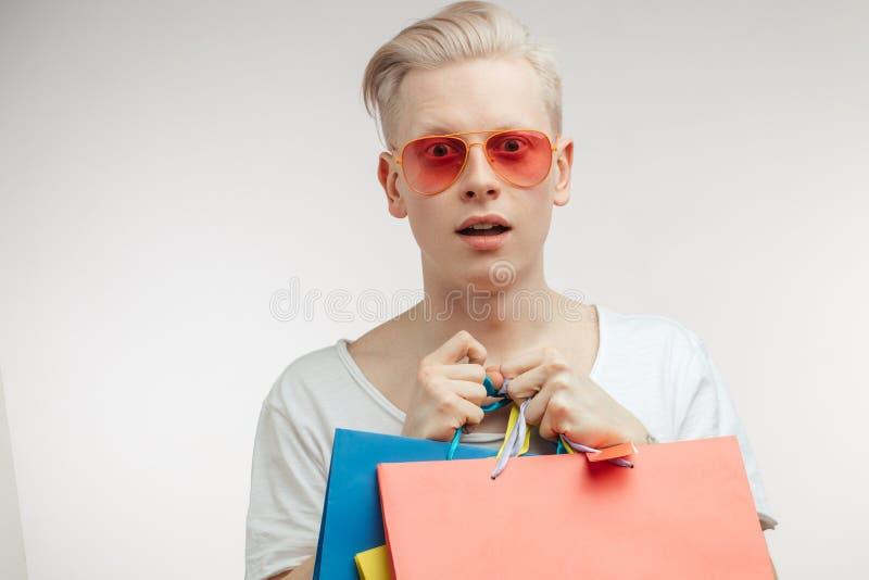 Retrato del hombre joven de la moda en vidrios rosados con los panieres fotos de archivo