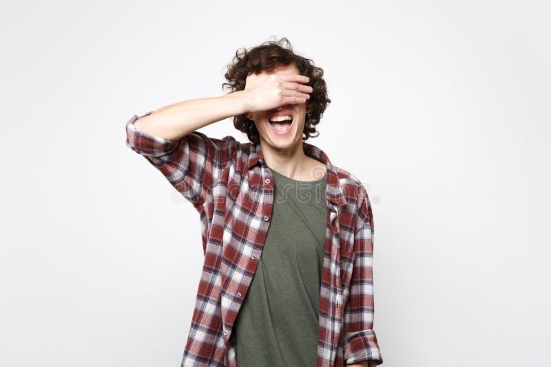 Retrato del hombre joven de risa alegre en la ropa casual que oculta, cubriendo ojos con la mano aislada en la pared blanca imagen de archivo