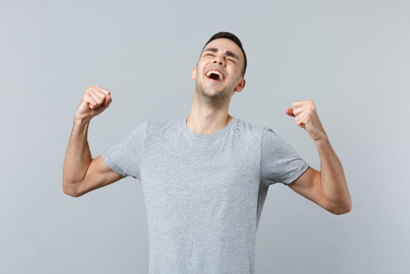 Retrato del hombre joven de risa feliz extático en puños de apretón de la ropa casual como el ganador aislado en la pared gris imagen de archivo libre de regalías