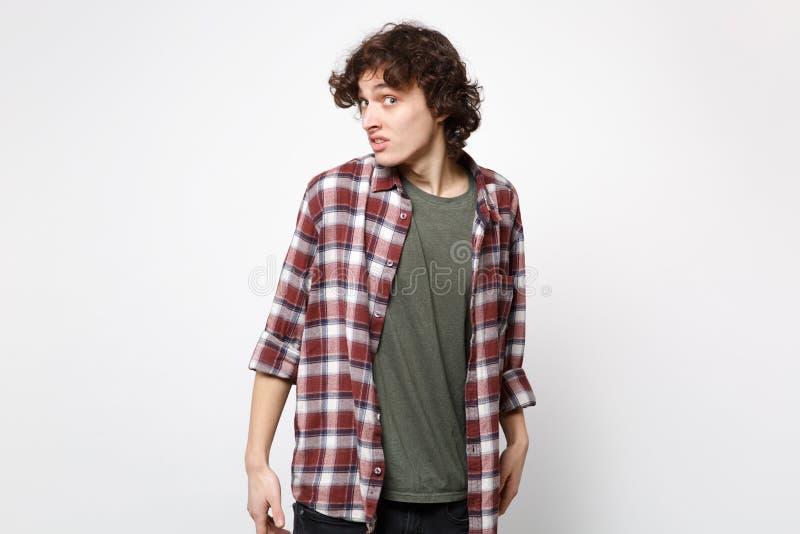 Retrato del hombre joven desconcertado desconcertante chocado en la ropa casual que se coloca, mirando la cámara aislada en la pa fotos de archivo