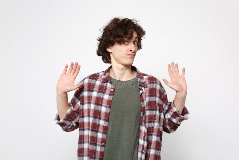 Retrato del hombre joven desconcertado en la ropa casual que mira la cámara, manos de extensión, mostrando las palmas aisladas en foto de archivo libre de regalías