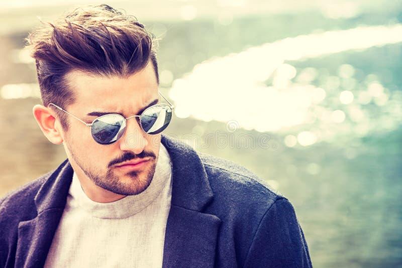 Retrato del hombre joven encantador con las gafas de sol al aire libre imágenes de archivo libres de regalías