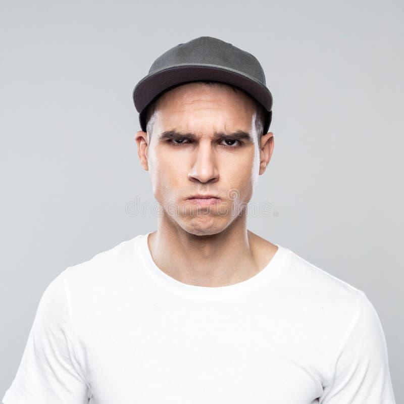 Retrato del hombre joven enojado en gorra de béisbol imagen de archivo