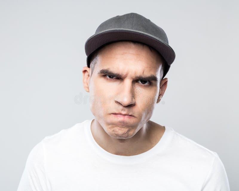 Retrato del hombre joven enojado en gorra de béisbol foto de archivo libre de regalías