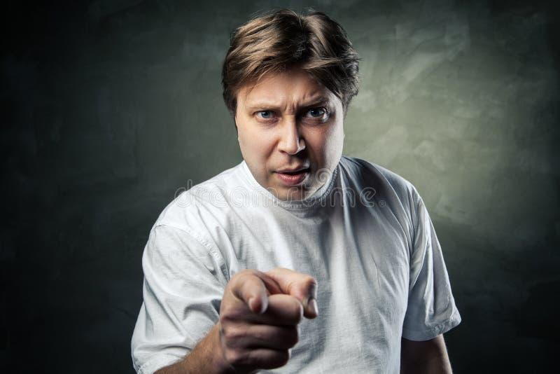 Retrato del hombre joven enojado que señala en usted imagen de archivo