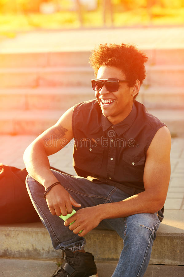 Retrato del hombre joven feliz en gafas de sol el día soleado imagenes de archivo