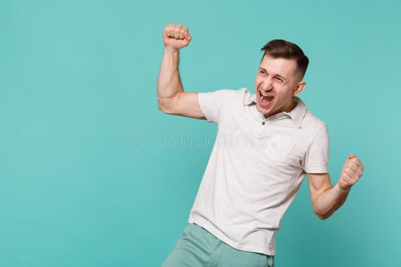 Retrato del hombre joven feliz en gesticular expresivo de la ropa casual con las manos, gritando aislado sí en azul foto de archivo libre de regalías