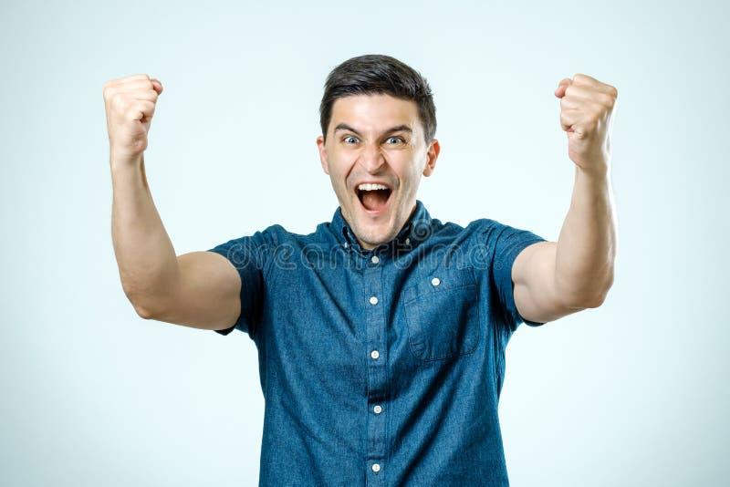 Retrato del hombre joven feliz que aumenta sus manos fotografía de archivo libre de regalías