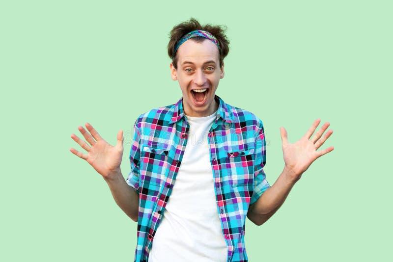 Retrato del hombre joven feliz sorprendido en la situaci?n a cuadros azul casual de la camisa y de la venda, de brazos aumentados imágenes de archivo libres de regalías