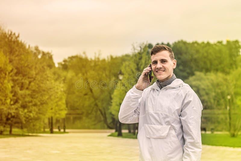Retrato del hombre joven fresco que sonríe y que habla en el teléfono celular imagenes de archivo