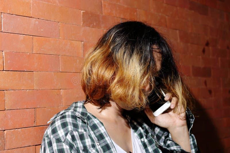Retrato del hombre joven hermoso andrógino como mujer hermosa que habla el teléfono elegante móvil en fondo de la pared de ladril imagen de archivo libre de regalías