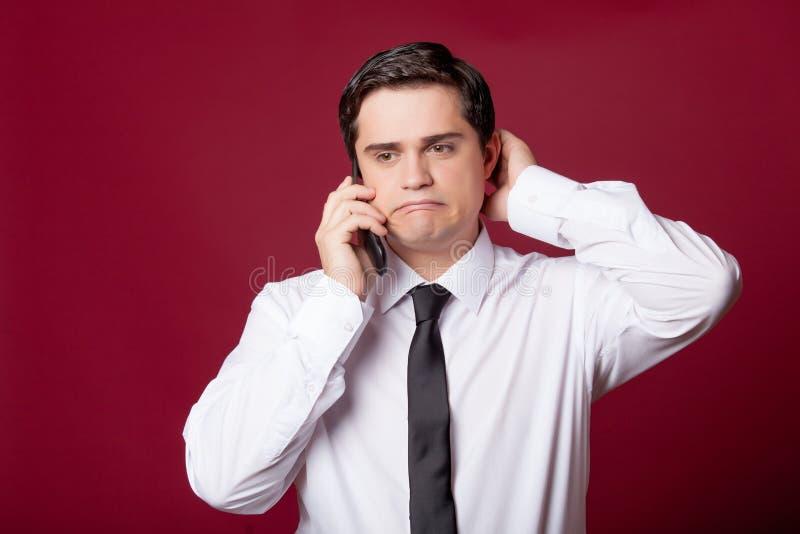 Retrato del hombre joven hermoso con el teléfono en el burgu maravilloso imagen de archivo