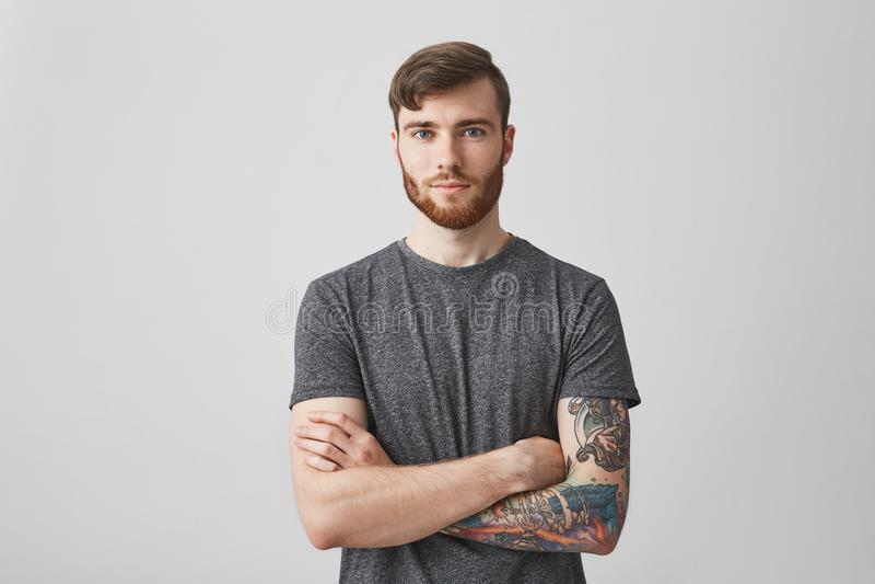 Retrato del hombre joven hermoso con la barba del jengibre y la mano tatuada que miran in camera con sonrisa y calma apacibles fotografía de archivo