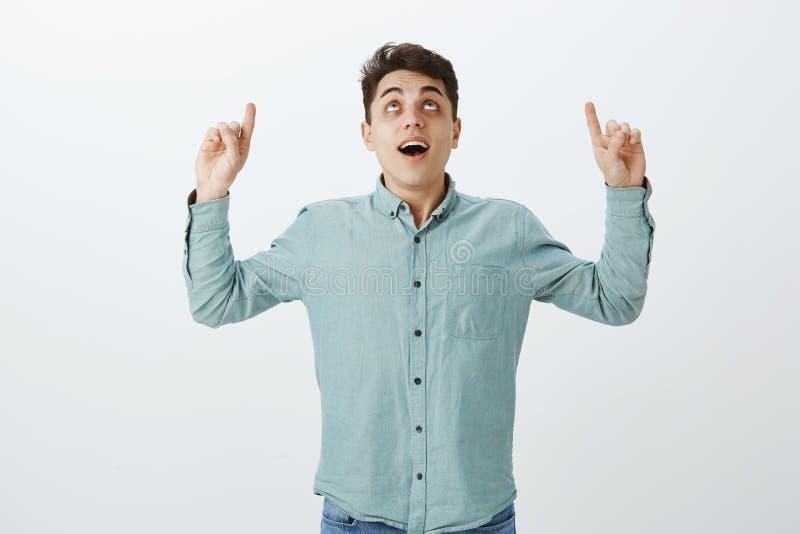 Retrato del hombre joven hermoso intrigante en camisa sport, aumentando los dedos índices y mirando para arriba con el mandíbula  imágenes de archivo libres de regalías