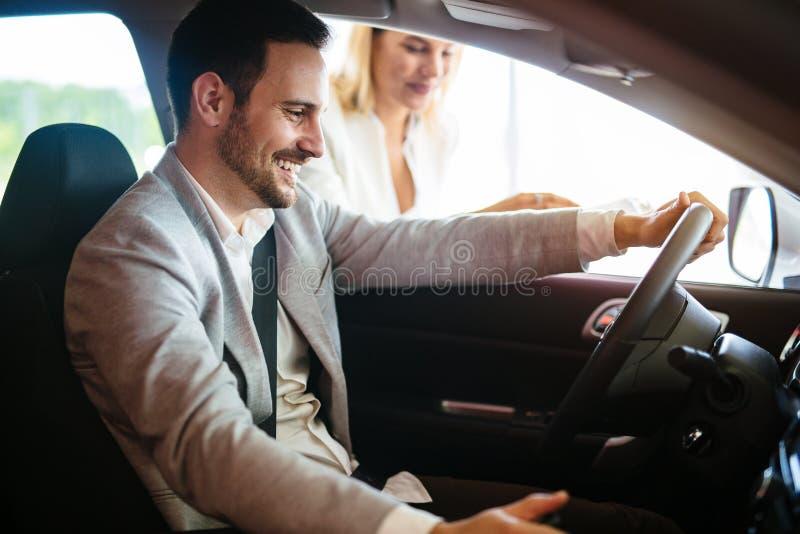 Retrato del hombre joven hermoso que toma el coche de lujo para la prueba de conducción, sentarse interior y sonreír foto de archivo