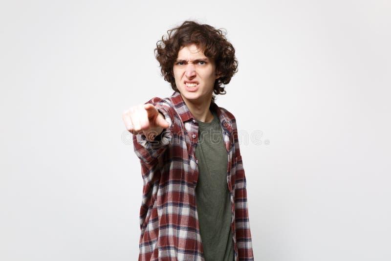 Retrato del hombre joven nervioso irritado en ropa casual que señala el dedo índice en la cámara aislada en la pared blanca fotografía de archivo