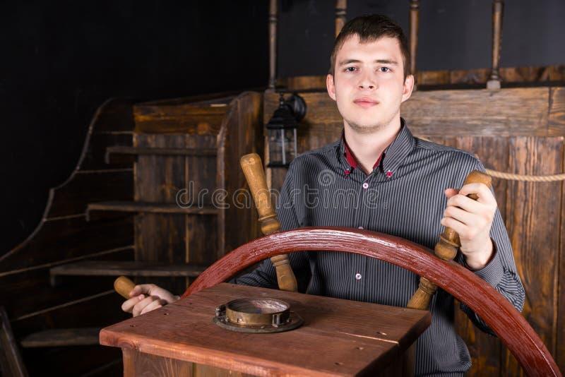 Retrato del hombre joven que dirige la nave de madera imagenes de archivo
