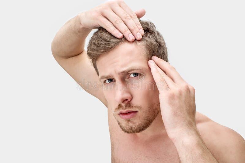 Retrato del hombre joven que mira en cámara Él lleva a cabo las manos en el pelo Él es preocupante Aislado en el fondo blanco fotografía de archivo libre de regalías