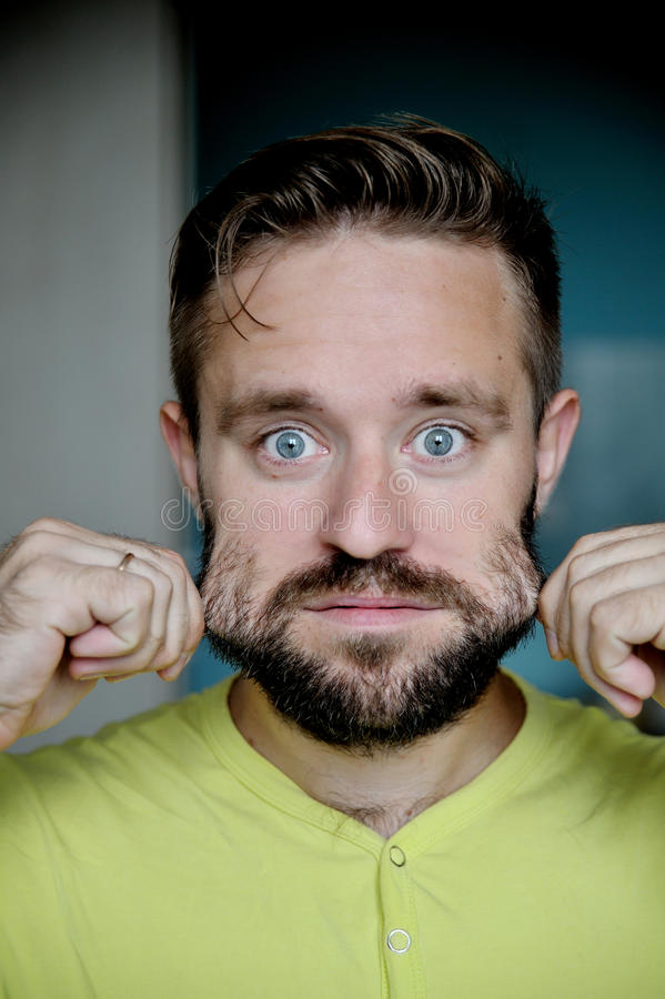 Retrato del hombre joven que tira de su barba imagen de archivo