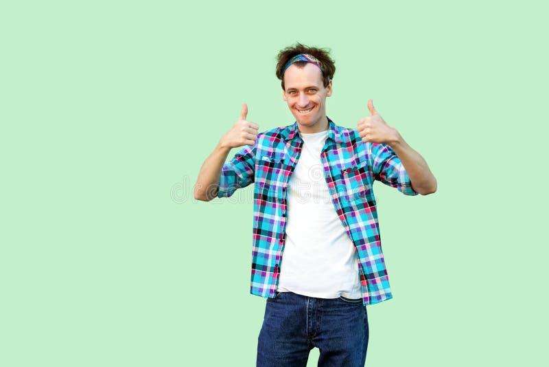 Retrato del hombre joven satisfecho en la situación a cuadros azul casual de la camisa y de la venda, pulgares para arriba y mira imagen de archivo libre de regalías