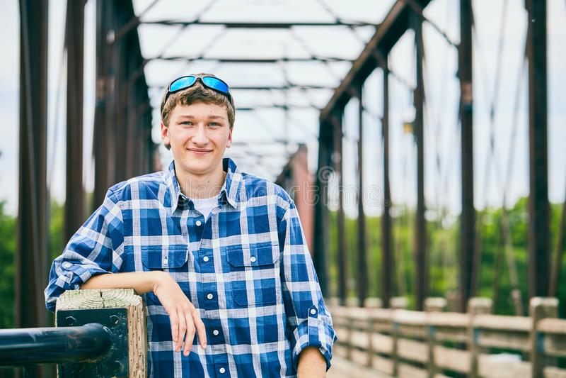 Retrato del hombre joven sonriente que se coloca en el puente foto de archivo