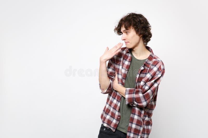 Retrato del hombre joven sorprendente chocado en la ropa casual que mira a un lado, guardando la mano cerca de boca, cara aislada fotos de archivo