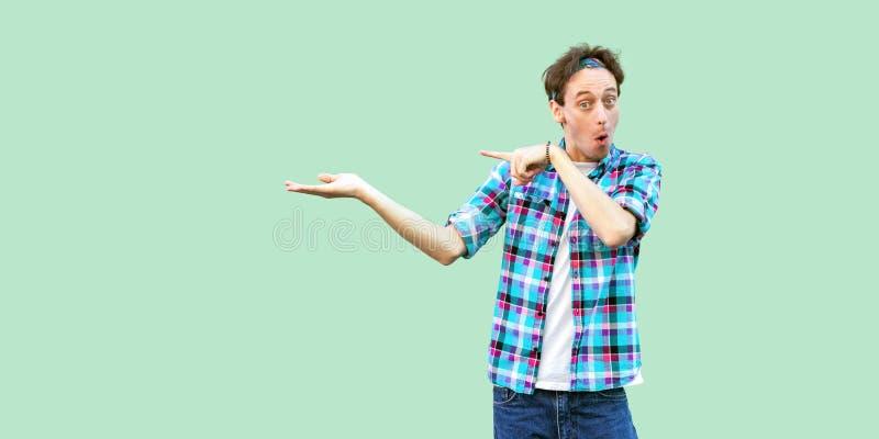 Retrato del hombre joven sorprendido en la situación a cuadros azul casual de la camisa y de la venda que mira la cámara con la c imagenes de archivo