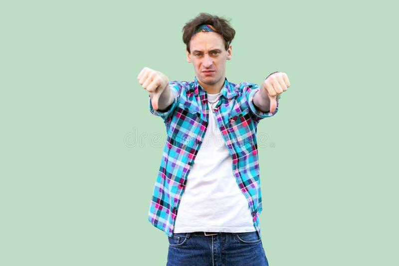 Retrato del hombre joven triste en la situación a cuadros azul casual de la camisa y de la venda, pulgares abajo y mirando la cám imágenes de archivo libres de regalías