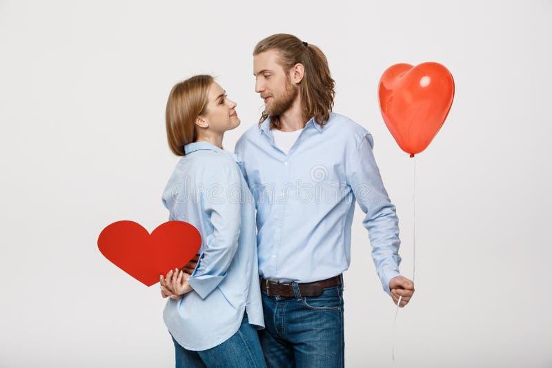 Retrato del hombre joven y de la mujer que sostienen un globo y un papel en forma de corazón fotos de archivo libres de regalías