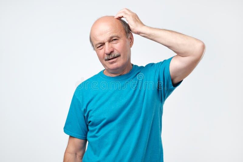 Retrato del hombre maduro casual en camisa azul que piensa y que parece desconcertado foto de archivo libre de regalías