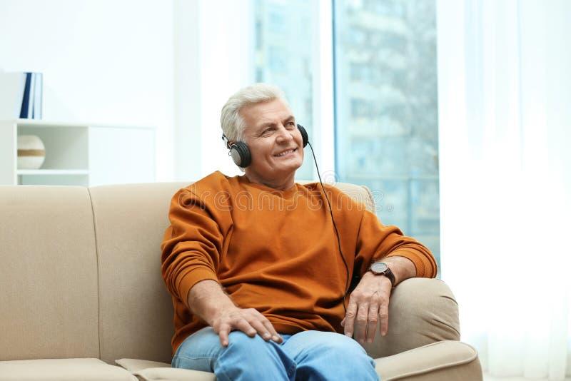 Retrato del hombre maduro con los auriculares en el sofá foto de archivo libre de regalías