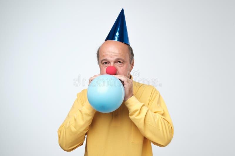 Retrato del hombre maduro en camiseta amarilla y el casquillo divertido que soplan un globo azul sobre un fondo blanco imágenes de archivo libres de regalías