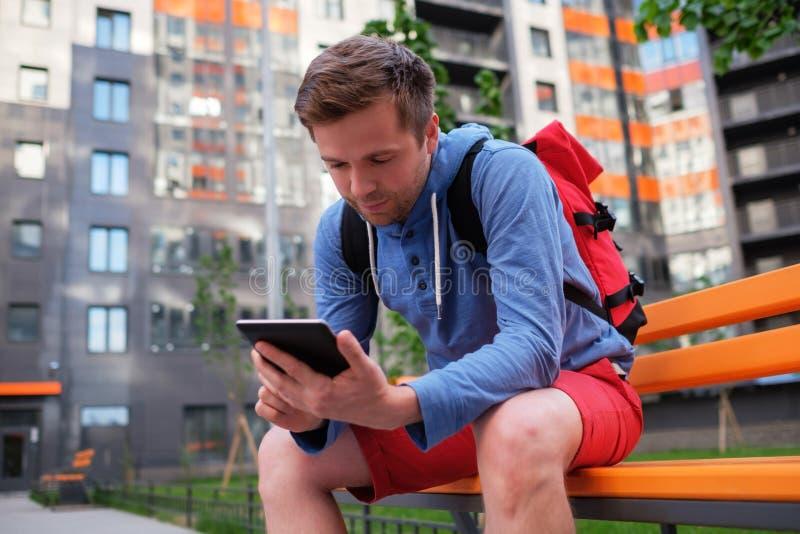 Retrato del hombre maduro en ropa informal usando la tableta digital al aire libre foto de archivo