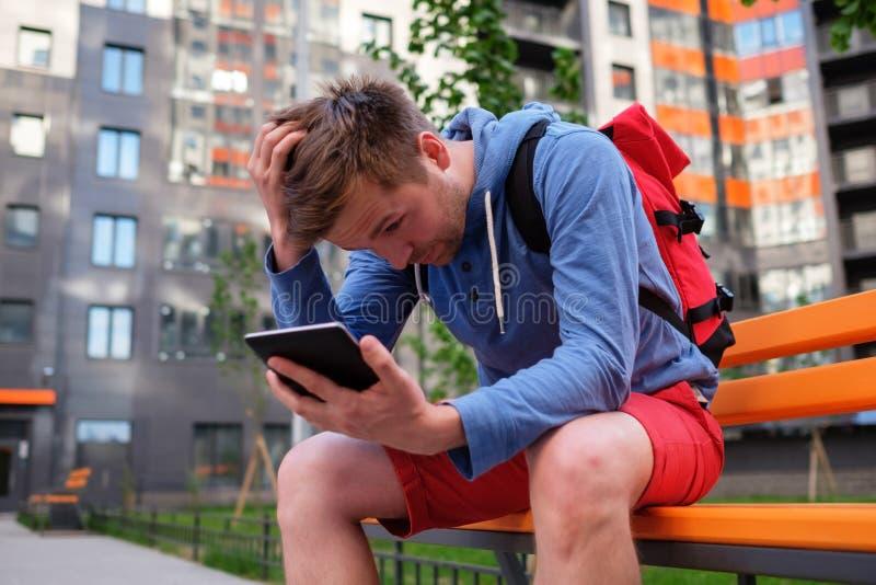 Retrato del hombre maduro en ropa informal usando la tableta digital al aire libre fotografía de archivo
