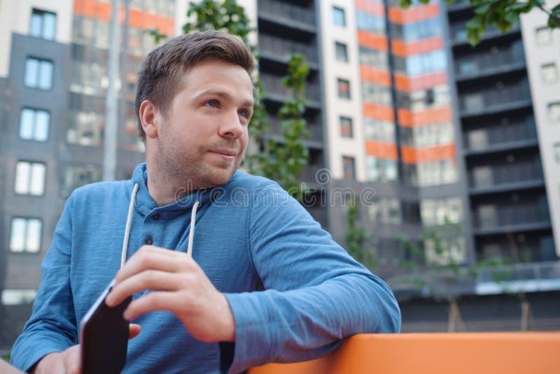 Retrato del hombre maduro en ropa informal usando la tableta digital al aire libre imagen de archivo