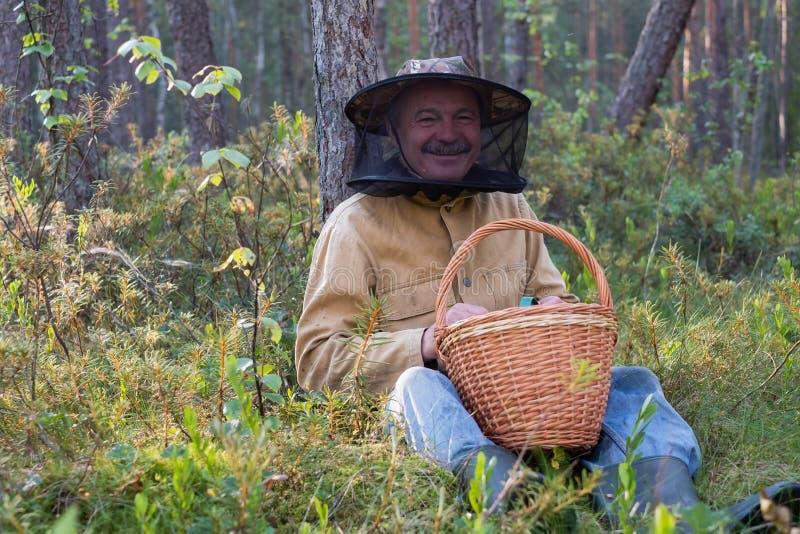 Retrato del hombre maduro relajado que se sienta en el bosque con la cesta foto de archivo libre de regalías