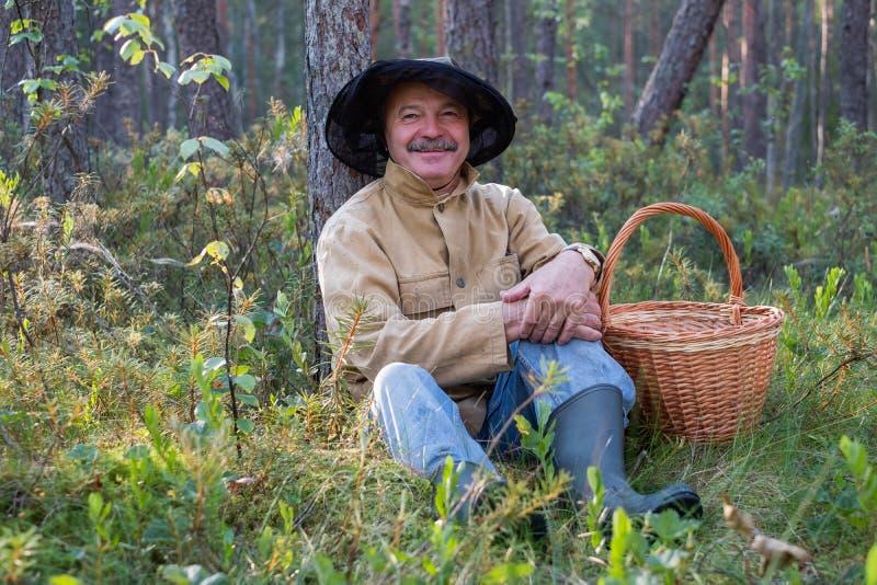 Retrato del hombre maduro relajado que se sienta en el bosque con la cesta fotografía de archivo libre de regalías