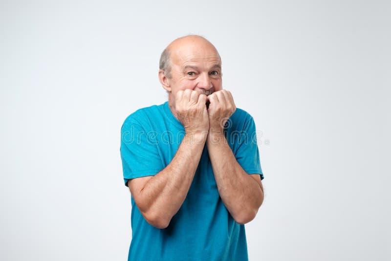 Retrato del hombre mayor ansioso en camiseta azul que muerde sus fingeres de los clavos freaking hacia fuera fotografía de archivo libre de regalías